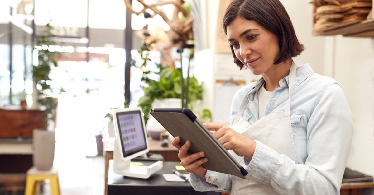 Female Owner With Digital Tablet Standing Behind Sales Desk